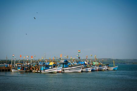 Colorful fishing boats with blue and white hulls and Indian flags on the masts, on the fishing pier in Goa. Wooden boats in the light of morning sun, birds flying in the sky. India independence day.