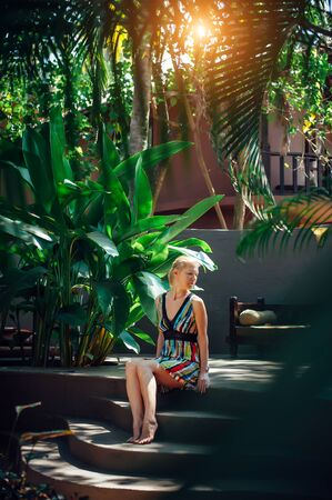 Young woman sitting in the shade of tropical trees on sunny summer day. Cute blonde is resting at spa resort. Calm secluded vacation.