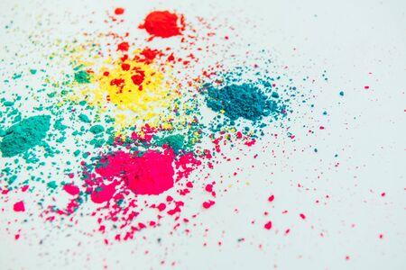 Abstraktes Mehrfarbenpulver gemischt auf weißem Hintergrund. Frieren Sie die Bewegung des Farbpulvers ein. Konzept indisches Festival Holi.