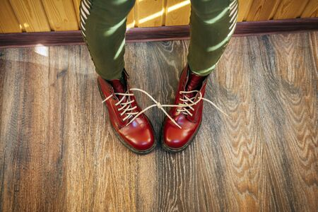 Female legs in stylish bright red boots with thick white laces tied together on wooden background, top view. Woman in funny pants and big size shoes. April Fools' day, pranks and fun.