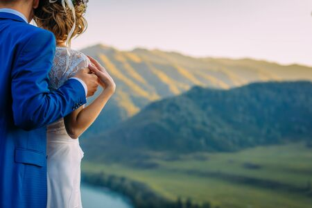 wedding theme, holding hands newlyweds with a perfect view of mountains and river Stock Photo