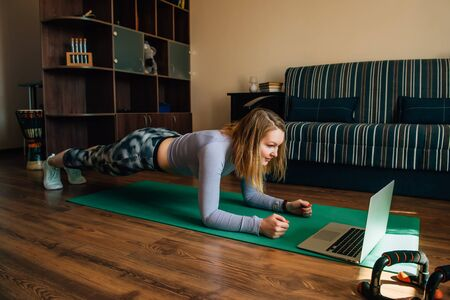 Young woman in sportswear doing plank on mat at home during quarantine. Remote workout for the period of coronavirus pandemic. Life in self-isolation.