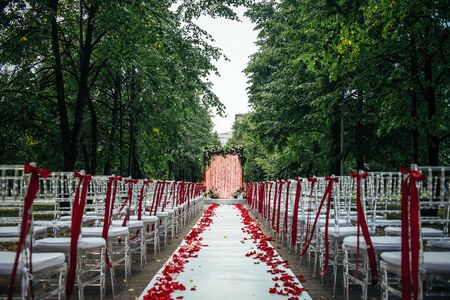 Passage between the chairs, decorated with rose petals leads to the wedding arch. Solemn wedding registration in the park among the green trees. Фото со стока