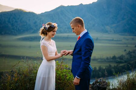 Newlyweds on wedding ceremony on background of mountains. The bride is dressed in classic white wedding dress, the groom is wearing in suit with a red tie Banque d'images