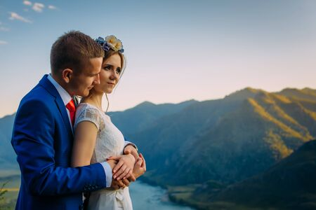 Young newly wed couple, bride and groom kissing, hugging on perfect view of mountains, river and blue sky