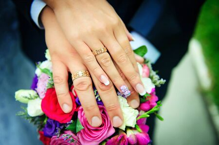 Hands of newlyweds on the background of wedding bouquet. Gold wedding rings on the finger of bride and groom, close-up. Concept of a wedding celebration.