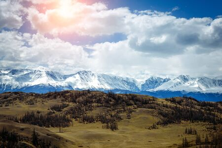 Amazing mountain landscape. Rocky mountains with snowy peaks, hills covered with grass in the Alpine scene on a bright sunny day with blue sky and clouds. View of steppe and snow-covered mountains.