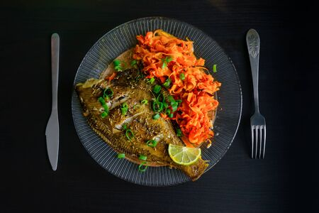 Baked fish flounder with lemon, carrot and spicy herbs, closeup on black background. Delicious fish dish with vegetables for healthy and proper nutrition. Fork and knife next to the plate, top view.