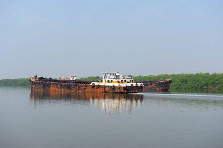 Natural landscape. Water transport. Barge floating on the river. Cargo ship, Mandovi River in Goa, India. Stockfoto