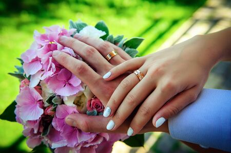 Hands of newlyweds with beautiful gold rings, close-up. Delicate lilac bouquet, stylish manicure. Perfect wedding ceremony concept.