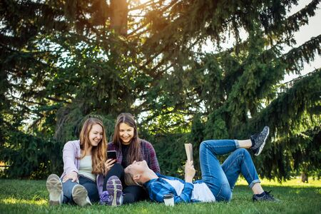 Three cute girlfriends resting the park. Young attractive girls on a green lawn talking and laughing. Concept of outdoor recreation, warm weather and a pleasant holidays.