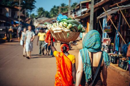 An Indian woman in red Sari carries a large basket of vegetables on her head. Tourists and locals in India. A crowded street in Gokarna, Karnataka.