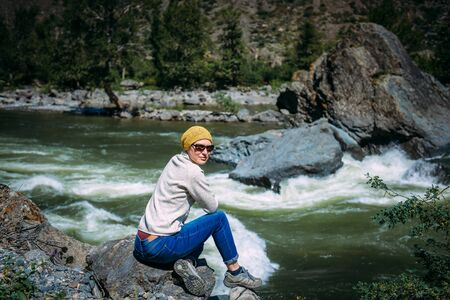 A young woman in sunglasses near the mountain river. Green river between the rocks and a girl sitting on the stone. A girl looking at camera, close-up. The river Chulyshman, Altai, Russia.