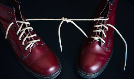 Stylish red shoes with laces linked together on black background. High boots with shoelaces connected together, close-up. Concept of April fool's day, joke, prank.