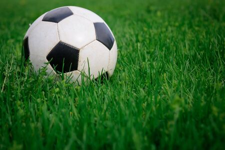 Soccer ball on the lawn on sunny summer day, close-up. White and black ball on background of green grass, copy space. Concept of active recreation, sports entertainment in nature. Foto de archivo