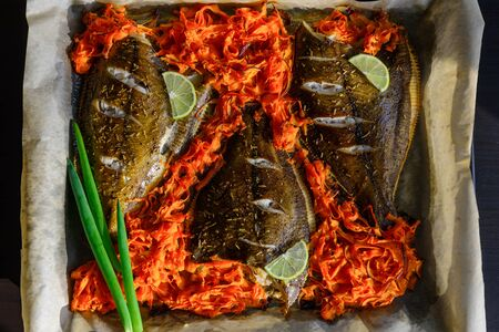 Fish baked on baking sheet with vegetables, close-up. Flounder on parchment with carrots, lime and green onions. Sea fish is a source of iodine, protein and essential fatty acids. Seafood recipes.