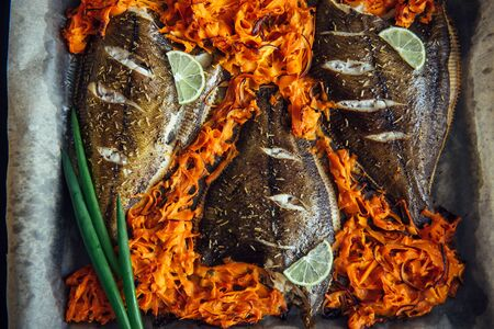 Fish baked on baking sheet with vegetables, close-up. Flounder on parchment with carrots, lime and green onions. Sea fish is a source of iodine, protein and essential fatty acids. Seafood recipes. Stock Photo