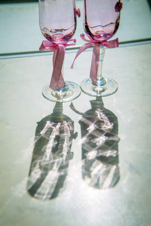 Wedding champagne glasses decorated with pink ribbons, close-up, vertical photo. Wine glasses for the bride and groom in the sunlight cast a beautiful shadow.