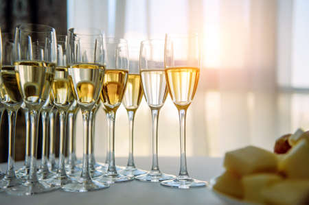 A row of glasses filled with cold champagne lined up, ready to be served. Glasses with Martini on the table - party background. Welcome drink on the wedding ceremony. 版權商用圖片 - 151484905