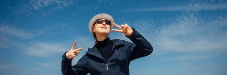 Cheerful woman in white hat and sunglasses poses against beautiful blue sky with feathery clouds. Stylishly dressed girl smiles and gestures with her hands. Happiness, positive, pleasure, joy.