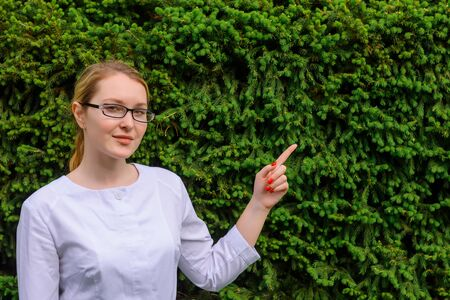 Female doctor with finger point up. Nutritionist in white coat and glasses on green foliage background with copy space. Image for advertising scientific developments in the food and medical industry.