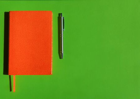 Bright orange notepad and stylish grey pen on green background with copy space. Concept of office products, diaries. Banque d'images