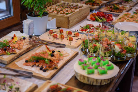 Festive buffet with a variety of cold snacks, selective focus. Catering for special events. Several a La carte dishes on the banquet table.