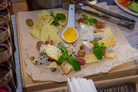 Cheese plate decorated with fresh mint leaves, close-up. Delicious appetizers of different types of cheese served with honey, cracker and grapes. Perfect accompaniment to wine. 版權商用圖片 - 151484767