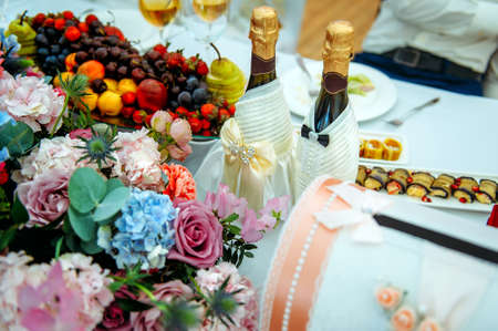 Beautiful festive table for the newlyweds, close-up. Champagne bottles are decorated with lace. Flowers, glasses, snacks, fruit. Concept of wedding celebration, banquet.