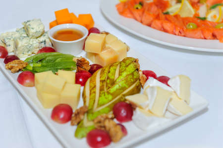 Cheese plate at banquet, close up. Assorted different types of cheeses with honey decorated with nuts, pear, kiwi, grape on large white dish. 版權商用圖片