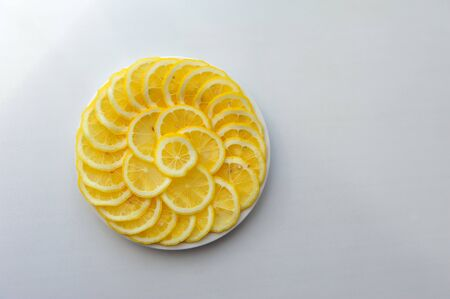 Lemon cut into slices on a white plate. Juicy round pieces of yellow lemon. Citrus is a source of vitamin and ascorbic acid. 版權商用圖片