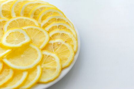 Lemon cut into slices on a white plate. Juicy round pieces of yellow lemon. Citrus is a source of vitamin and ascorbic acid. Copy space. 版權商用圖片