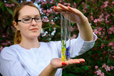 Female scientist in glasses and white coat with test tubes in her hands studies the properties of plants in botanical garden. Creating floral scents, natural cosmetics, herbal medicine, perfumes.