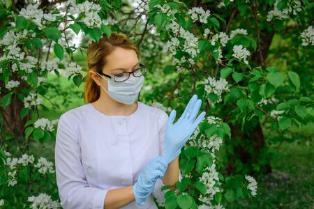 Female botanist in white coat, medical mask and glasses puts on gloves, works with plants in botanical garden against the flowering tree. Portrait of young and beautiful woman doctor, working outdoor. 版權商用圖片