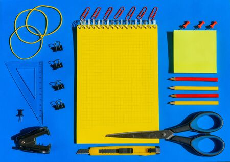 School supplies top view close-up, laid out on a blue paper, solar lighting. Yellow-blue office supplies background. Copy space for text on notepad. 版權商用圖片 - 149250757