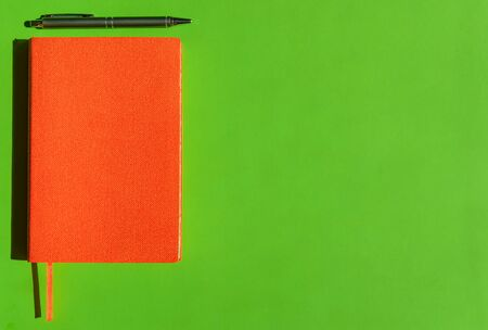 Bright orange notepad and stylish grey pen on green background with copy space. Concept of office products, diaries.