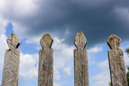Old wooden fence against sky with clouds. Dilapidated village fence on a cloudy day. Silence and desolation. 版權商用圖片