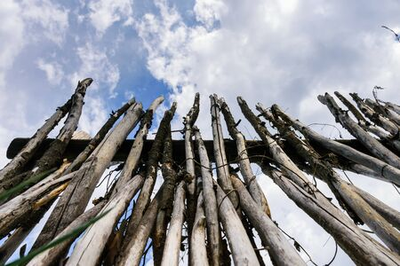 Sharp stakes of palisade stand upright against cloudy sky, view from below. Old village fence made by the hands of a farmer.