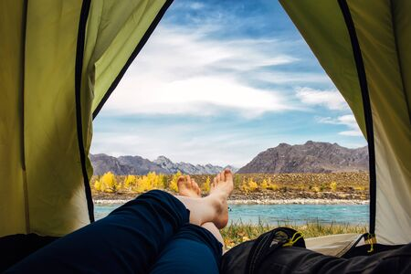 Women's bare feet in blue trousers crossed on the edge of green tourist tent. Turquoise river against rocky mountains and blue sky. View from an open tent with copy space. Freedom concept.