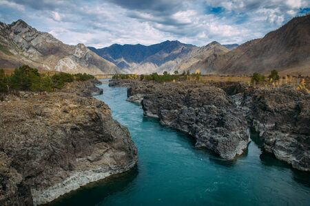 Turquoise Katun river in gorge is surrounded by high mountains under majestic autumn sky. A stormy mountain stream runs among rocks - landscape of the Altai mountains, beautiful places of the planet. 版權商用圖片