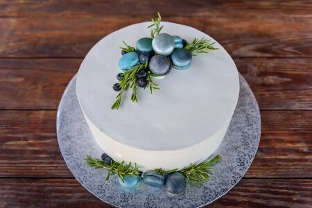 Stylish cake on wooden background, top view, close up. Wedding cake with white icing decorated with macaroons, blueberries, rosemary sprigs. Handmade confectionery.