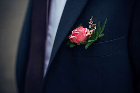 Boutonniere of fresh flowers on the suit of groom. Red rose in a buttonhole, close-up. 版權商用圖片 - 154876044