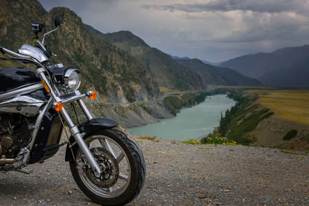 Motorcycle on the background of mountain river and rocks. Action camera is mounted on the motorbike steering. Concept of freedom, active recreation, and motorcycle rides.