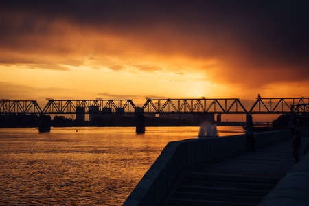 Urban evening landscape. Railway bridge over the river at sunset. Fantastic clouds in the dark sky. 版權商用圖片 - 154875866