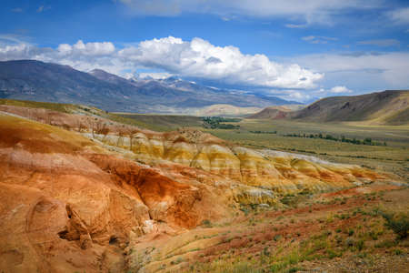 Amazing natural phenomenon-Martian landscapes in the Altai mountains. Multicolored rocks against a blue sky with white clouds. Futuristic panoramic picture, background image. Mars. 版權商用圖片 - 154876181