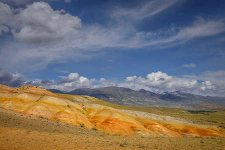 Amazing natural phenomenon-Martian landscapes in the Altai mountains. Multicolored rocks against a blue sky with white clouds. Futuristic panoramic picture, background image. Mars. 版權商用圖片 - 154875026