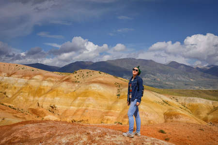 Young woman in jeans and sunglasses stands against beautiful mountains and blue sky on sunny day. Freedom, adventure, discovery, travel available to ordinary people.