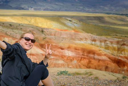 Female traveler takes a selfie sitting on hill on the background of Martian landscapes in Altai mountains. Young girl smiles the camera and shows hand gesture. Image for advertising with copy space. 版權商用圖片 - 154874915
