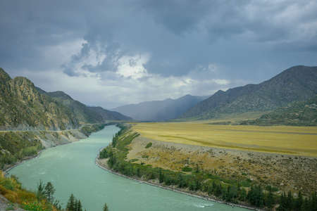 Majestic mountain landscape on a rainy summer or autumn day. Beautiful view of the bend of Katun river, plains and rocks. Torrents of rain, overcast sky. Natural backgrounds.
