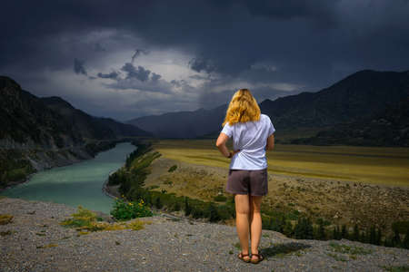 Young woman in white t-shirt standing back to the camera in the sunlight and looks at the beautiful view of Katun river, plains and rocks. In the distance, torrents of rain, overcast sky. 版權商用圖片